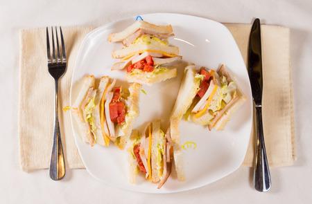 doubledecker: Overhead of Triple Decker Sandwich on Plate at Place Setting Stock Photo