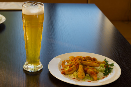 Fried Main Dish on White Round Plate and Glass of Beer Served on Wooden Table at the Restaurant. photo