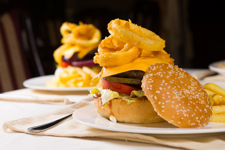 restuarant: Gourmet Cheeseburgers Piled High with Toppings on Plates on Restuarant Table Stock Photo