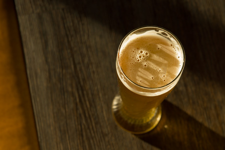 Overhead of Glass of Beer on Table in Sunlight