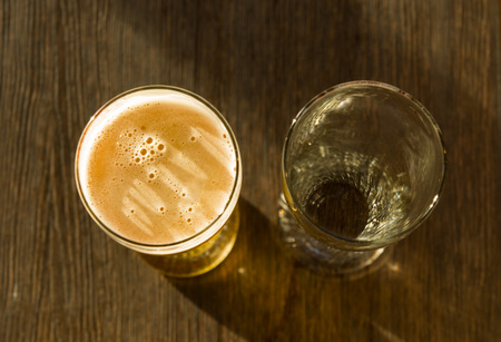 glass of beer: Overhead of Glass of Beer Beside Empty Glass on Wooden Table