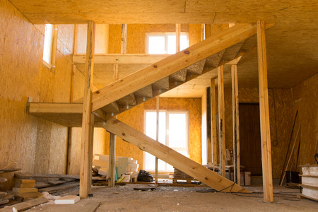Incomplete Architectural Wooden Interior Design with Stairs, Illuminated with Sunlight photo