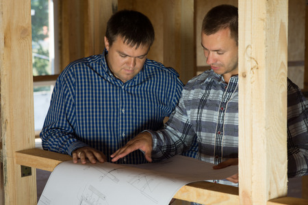 Two Middle Age Building Interior Designers Talk About the Proposed Design on Blueprint. photo