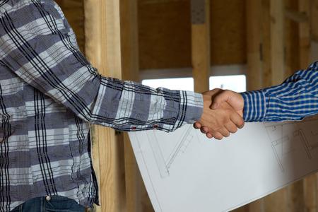 建築家と両方長いスリーブ シャツを示すハンドシェイクで背景に青写真とクライアントを閉じます。承認済みの設計を強調しています。 写真素材
