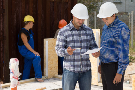 perturbed: Engineer and architect wearing hardhats standing discussing paperwork on a construction site with builders working behind them
