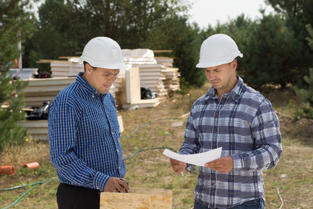 perturbed: Two engineers having a discussion on site as they stand discussing a document with stacks of insulated wooden panels in view behind