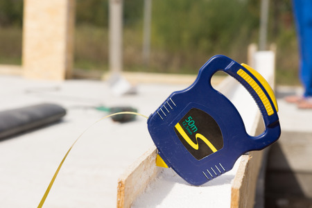 retractable: Builders blue plastic retractable tape measure resting on an insulated wall panel on a building site Stock Photo