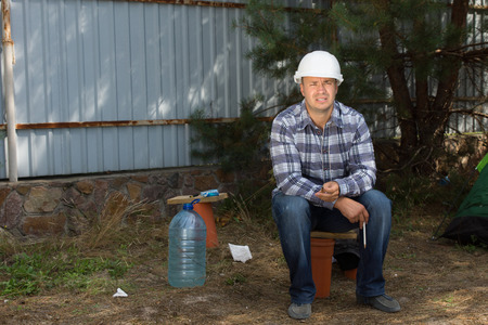 Tired Male Civil Engineer Sitting at the Corner in Construction Site While Looking at Building Progress.