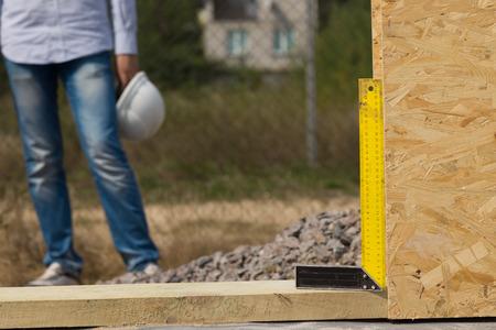 perpendicular: Costruttori cercano angolo retto oa destra in uso in un cantiere edile al fine di garantire che un pannello parete in legno � esattamente perpendicolare