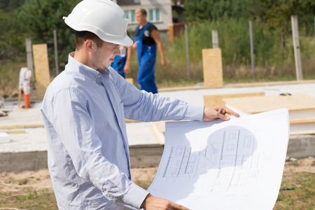 Young architect checking a structural drawing or blueprint as he stands on the building site of a new house photo