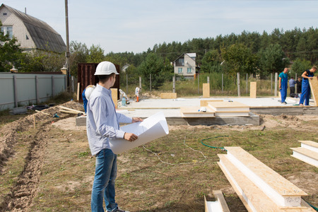 Foreman checking building supplies on site standing in front of a stack of lumber and timber with a blueprint in his hands watching workmen working photo