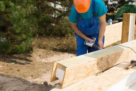 Workman het boren van een gat in een houten bekleed geïsoleerde