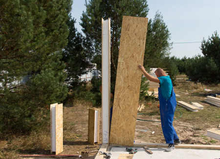 erecting: Worker in overalls standing erecting insulated wooden wall panels on a building site of a new house Stock Photo