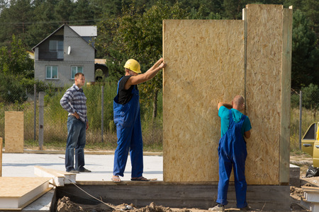 Team of young builders erecting prefabricated wall panels on a building site of a new house photo
