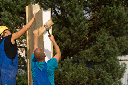 aligning: Two builders erecting insulated wooden wall panels on a new house carefully aligning them for installation Stock Photo