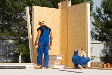 erecting: Two Male Construction Workers Busy in Building Real Estate House
