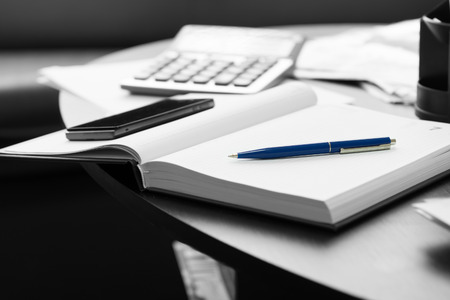 summation: Close up White Memo Notebook with Blue Pen and Mobile Phone on Black Round Table. Stock Photo
