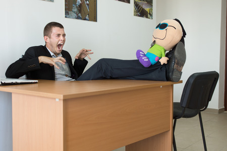 unmotivated: Young Male Office Worker Playing with Stuffed Toy, with Feet on the Table, Showing Monster Face at Office.