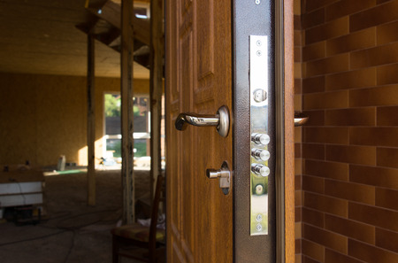 quotations: Safety lock on a new wooden front door showing the three security cylinders required by insurance companies for best premium quotations