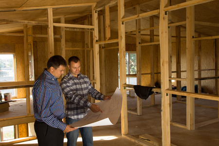 Two builders standing with an open blueprint discussing the interior of a half completed timber frame house