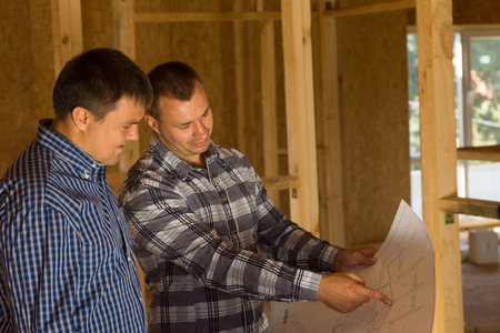 licensed: White Professional Male Building Architect and Client Discussing the Interior Building Design on the Blue Print.