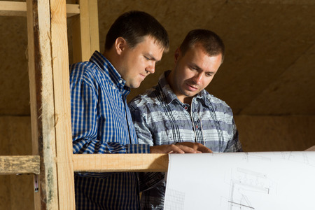 licensed: Two Middle Age Building Architects Reviewing Building Blueprint at the Site Seriously.