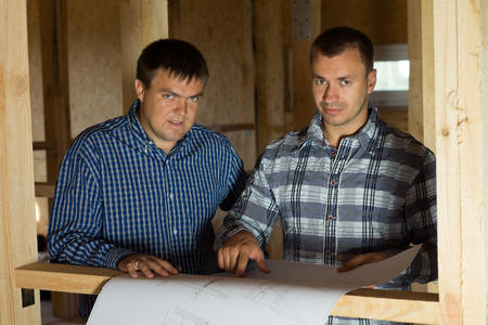Serious Middle Age Architect Men at Building Site with Blueprint Looking at Camera photo