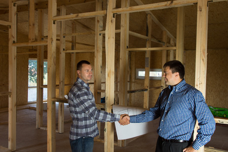 Male Engineer and Architect Showing Handshake at Building Site, Emphasizing Both Agreed to Project Design. photo