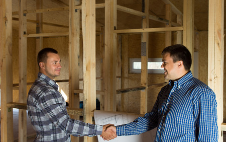 Two men shaking hands in a half constructed timber frame house with a building blueprint alongside them as they signal their satisfaction with the progress