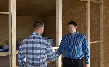 Middle Age Professional Engineer Men Showing Handshake at Building Site. Emphasizing Approved Project Proposal. photo