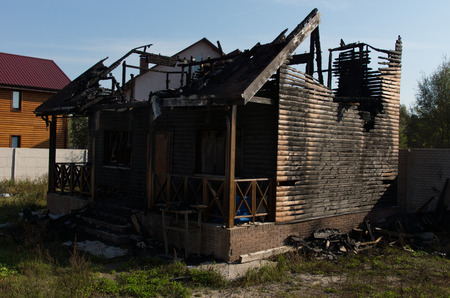 burnt out: Extensive Fire Damage of Architectural Real Estate Property on Grassy Landscape Caused by Negligence.