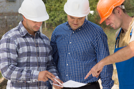 Builder, engineer and architect having a meeting standing discussing a document in their hardhats on a building site Stock Photo