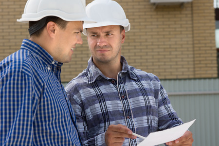 Middle Age Male Engineer and Foreman Discussing the House Project at the Construction Site. Stock Photo