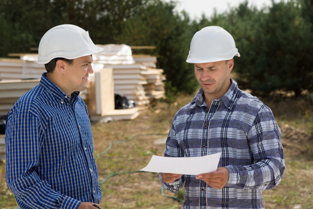 building planners: Close up Middle Age Building Planners Discussing the Construction Progress at the Site. Stock Photo