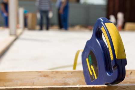retractable: Blue plastic retractable builders tape measure on a building site with copyspace for your text