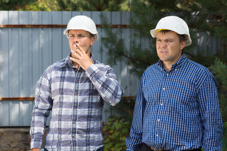 building planners: Two Middle Age Male Building Planners Visiting the Project Site While Looking at the Construction Progress.