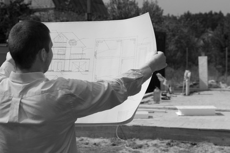 Architect checking the progress of a new build construction holding up his blueprint in front of him, monochrome image photo