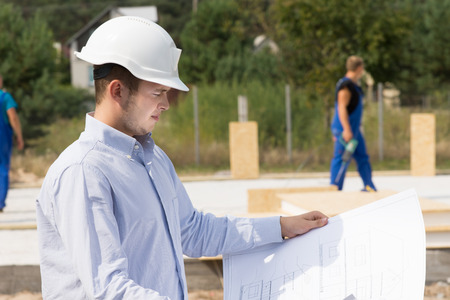Young architect or engineer checking specifications on a plan or blueprint as he stands overlooking the construction site photo