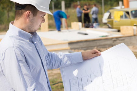 Architect standing studying a handheld blueprint on a construction site of a new build house photo