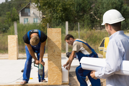 Architect or engineer on a building site watching workmen assembling prefabricated wall panels on a new build house photo