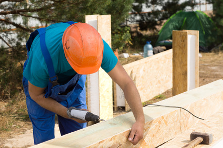 Workman drilling a hole in a wooden clad insulated beam on a new build construction site for a new house Stock Photo