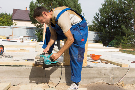 Carpenter sanding a wooden beam on a building site for a new house construction photo