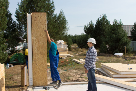 Group of builders erecting insulated wooden wall panels on the newly laid floor of a new build house on a residential plot photo