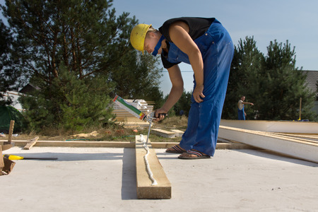 qualified worker: Builder or carpenter applying glue to a wooden beam on a construction site from a glue gun