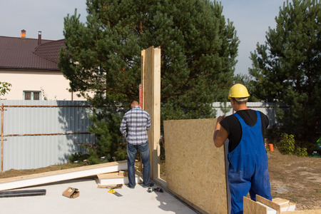 erecting: Workmen erecting wall insulation panels clad in wooden boards as they work on a new build house construction site