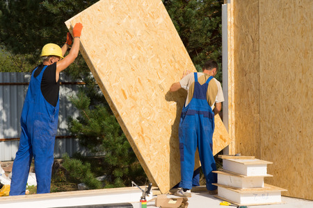 Construction workers positioning timber wall panels in a new build prefabricated wooden house