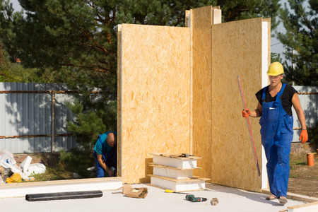 prefabricated buildings: Workmen busy erecting insulated walls on a construction site installing the corner units on the newly laid floor