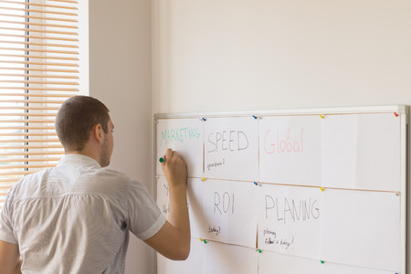 prioritizing: Young Male Office Worker Writing on Whiteboard for Work Schedule, Attached on the Interior Building Wall.