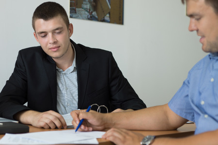 purchaser: Man signing a purchase agreement under the watchful eye of a salesman or estate agent as he completes a transaction Stock Photo
