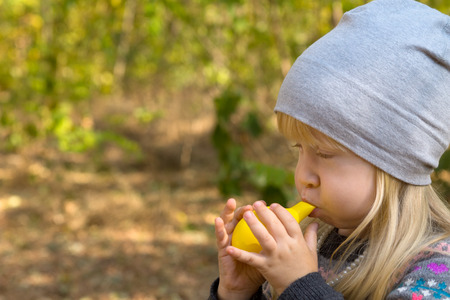 bonnet up: Close up Young Blond Kid in Gray Bonnet Blowing Yellow Balloon Toy for Fun. Outdoor Capture.